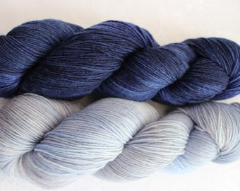 Two skeins of Luxurious Merino, Cashmere, Nylon yarn. One dark blue tonal skein and one light blue and grey tonal skein.