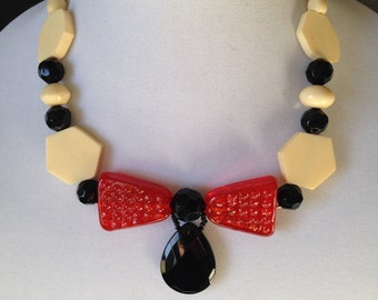 A bow shaped necklace, in orange, black and off white.