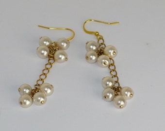 Pearl clusters on gold chain dangle earrings.