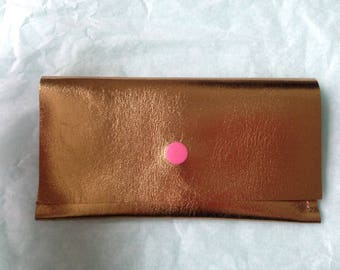 Gold leather clutch, pink clasp
