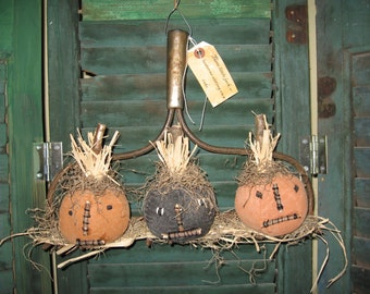 Three little jack-o-lanterns sitting on a rake