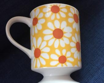vintage mug pedestal mug, footed mug. white with yellow and orange mod flowers, daisy