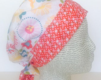 Tie Back Surgical Scrub Cap scrub hat featuring a white material with cute flowers in pink yellow red blue and green coordinating band 2t