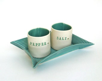 hand built porcelain salt and pepper cellars sitting on a tray