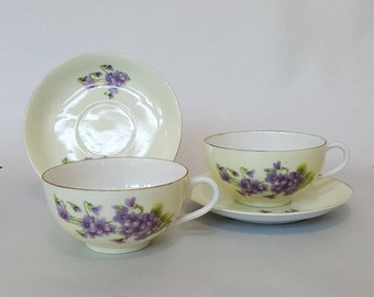 2 yellow eggshell porcelain cup and saucer decorated with purple flowers and gilt rim, unmarked