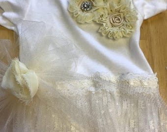Beautiful handmade baby girl onesie with lace and embellishments.