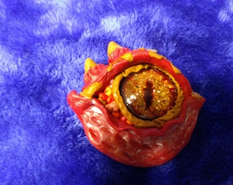 Fiery red, orange, tan hand-made polymer dragon's eye pendant with hand-painted sparkly fire-colored eyeball