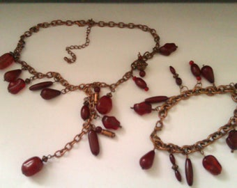 copper coloured necklace and bracelet set with red beads
