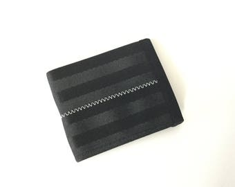 Black seat belt wallet with gray stitching