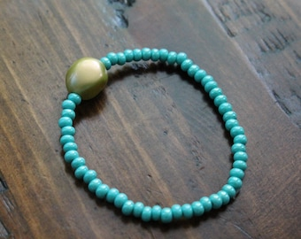 Gold bead with small blue beads Beaded Bracelet