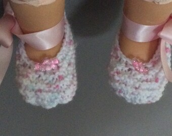 Pretty in pink. Newborn baby booties with pink satin ribbon and pink beads.