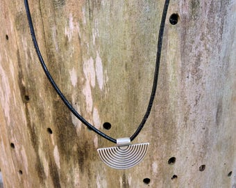 Ethnic half moon pendant necklace mounted on black leather cord