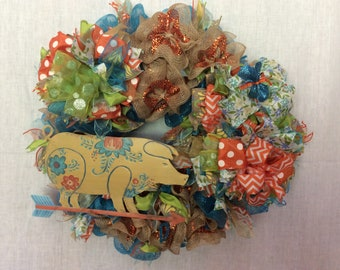 A fun pig deco mesh wreath with three beautiful fun bows in orange,blue and  green