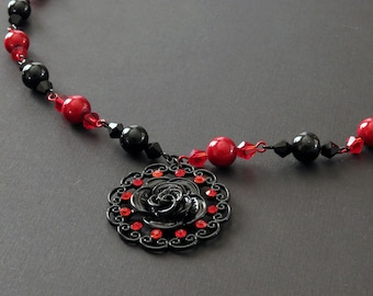 Red and black beaded necklace with rosette pendant and red glass pearl earrings