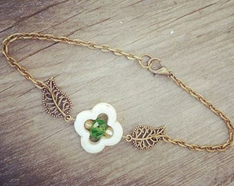Carved white turquoise flower bead with green crystal center stone, and antique brass filigree accent leaves