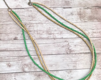 Green gold tan long beaded necklace. Long green beaded necklace.