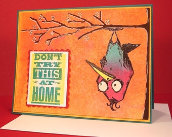 Funny Greeting Card featuring a Wonky Bird Hanging Upside Down from a Tree
