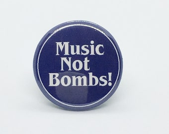 """Music Not Bombs! - 1 1/4"""" Pin, Zipper Pull, Keychain, Magnet or Hair Tie"""