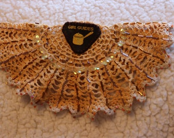 Upcycled doily brooch with brownie badge and sequins
