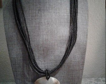Vintage 7 Strand Black Beaded Necklace with Large Flat Shell Pendant