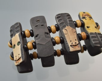 Tribal Faces in earthtones sculpted of porcelain handmade beads on stretchy elastic