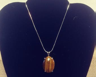 Oval Tiger Eye Cabochon with Silver Mounting has a chain.