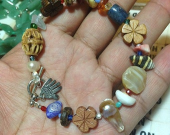 Maui mixed plate, island treasures bracelet, includes shells, wood, pearl, coral, seeds, and stones, plus sturdy toggle clasp.
