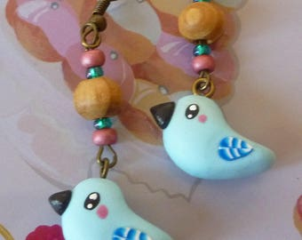 Earrings in bronze metal with a blue kawaii bird made with polymer clay and beads