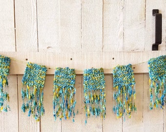 Hand woven banner in green, blue and yellow.