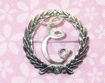 "Sterling silver initial ""E"" laurel wreath brooch."