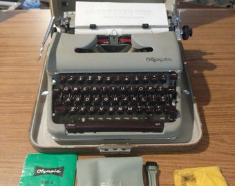 1960 Olympia SM4 portable typewriter with case, manual, and brush cool characters as well!
