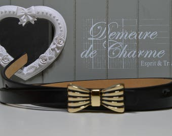 Black belt with a buckle bow shaped metal color gold