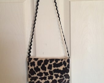Little girl denim and animal print  purse . Black Rick Rack strap and an animal print flap over purse. Cute accessory .