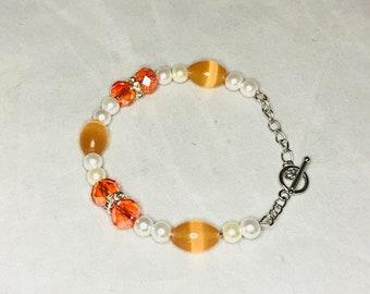 Orange and white memory wire beaded bracelet