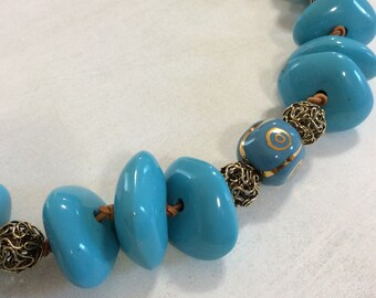 Turquoise blue resin nugget necklace. Gold plated filigree and Kazuri bead feature.Tan leather cord.