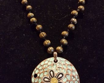 Copper sand dollar with .22 Remington casing in the center long wooden bead chain each one tied separate.