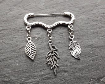 Silver coloured brooch with tree branch design pin and leaf dangles.