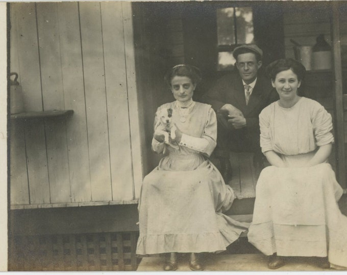Vintage Photo RPPC: Man, Two Women on Front Porch with Puppy, Early 1900s. Dark Rings Under Eyes [86691]