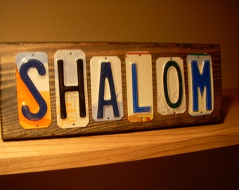 Shalom wall sign made from recycled license plates.