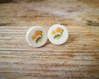 Ceramic stud earrings with vintage yellow flower on white background, retro , kitsch,shabby chic