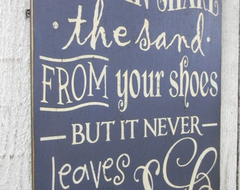 You can shake the sand from your shoes but it never leaves your soul - typography word art beach wood sign