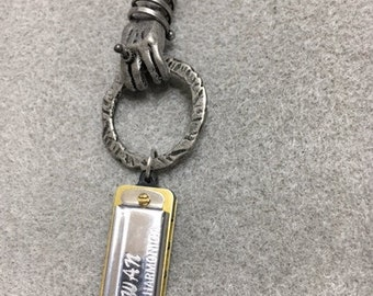Hand holding a Harmonica necklace
