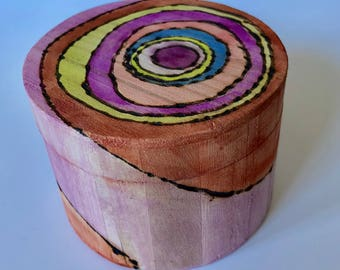 Round hand painted wood box with concentric circular design.