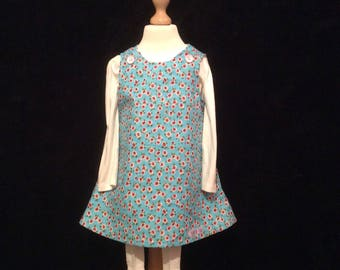 Pretty pink and blue reversible pinafore .