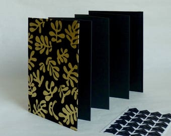 Photo album accordion, 12, 5 x 17, 5 cm, 14 black pages. Stylized floral motifs, Nepalese paper, black and gold.