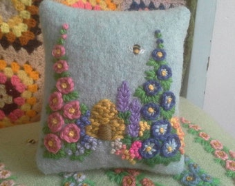 A hand embroidered pincushion with beehive, bee and flowers