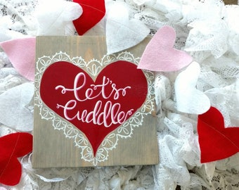 Let's cuddle heart wood sign.