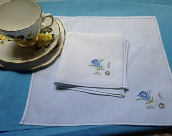Two vintage linen napkins with blue rose embroidery