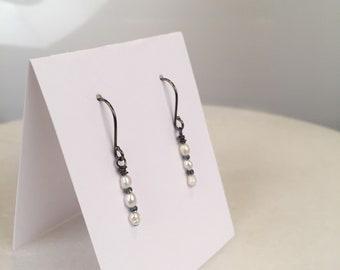 Petite Freshwater Pearl drop earrings on gunmetal