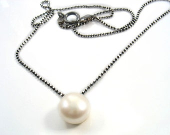 10 mm freshwater pearl sitting in a gold cup, held by a sterling black sparkling diamond-cut chain. Solitaire white pearl on black chain.